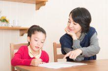 子供に勉強を教えるお母さん