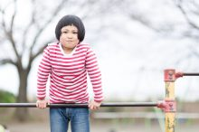 鉄棒の練習を頑張る子供